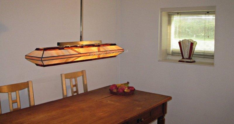 Silhouette 88 cm. een langwerpige Rose design Tiffany lamp hier hangend boven een eettafel.